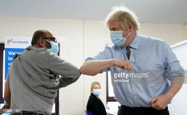 Prime Minister Boris Johnson elbow bumps Ismail Patel after getting his jab during a visit at a COVID-19 vaccination centre in Batley, on February 1,...