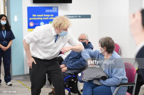 Prime Minister Boris Johnson elbow bumps people as he visits a coronavirus vaccination centre at the Health and Well-being Centre in Orpington,...