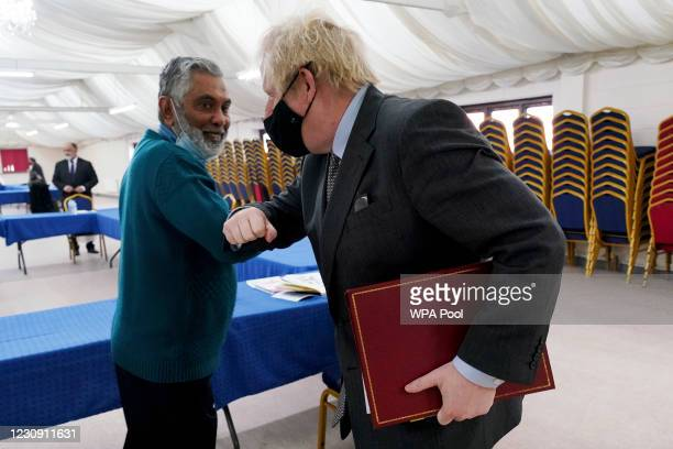 Prime Minister Boris Johnson elbow bumps with the Community leader Rafik Dabhad during a visit at a COVID-19 vaccination centre in Batley, on...