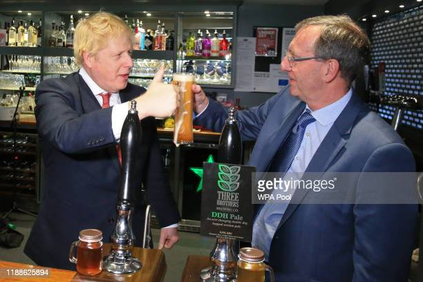 Prime Minister Boris Johnson gestures after pulling a pint with newly elected Conservative party MP for Sedgefield, Paul Howell at Sedgefield Cricket...