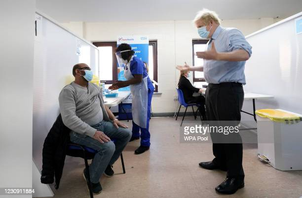 Prime Minister Boris Johnson gestures as doctor Chantelle Ratcliffe prepares the vaccine for Ismail Patel during a visit at a COVID-19 vaccination...