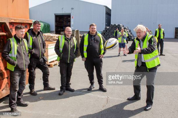 Prime Minister Boris Johnson gets thrown a rugby ball whilst talking to some of the staff at his visit to Next World Sports as he campaigns in Wales...