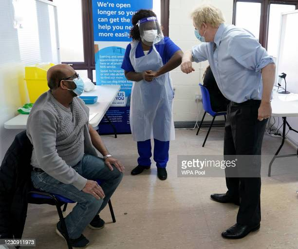 Prime Minister Boris Johnson greets doctor Chantelle Ratcliffe before she administers the vaccine to Ismail Patel during a visit at a COVID-19...