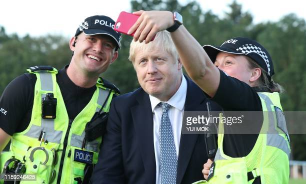 Prime Minister Boris Johnson has a selfie taken as he arrives to meet emergency crews at Whaley Bridge Football Club in Derbyshire as work continued...