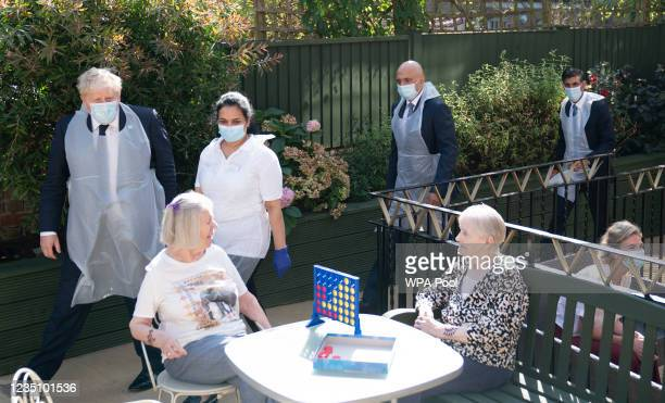 Prime Minister Boris Johnson , Health Secretary Sajid Javid and Chancellor of the Exchequer Rishi Sunak talk to residents Doreen and Janet during a...