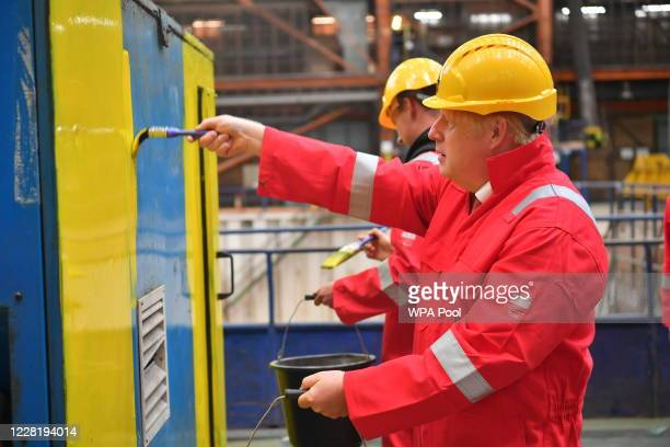 Prime Minister Boris Johnson helps out with the painting of an electrical generator with Sam Evans during his visit to Appledore Shipyard in Devon...