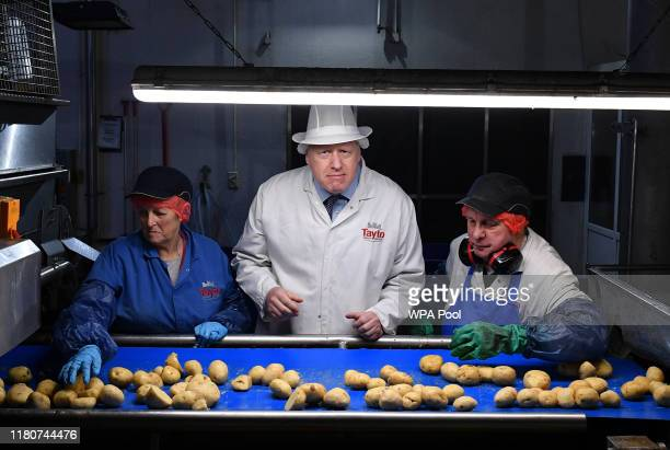 Prime Minister Boris Johnson helps quality control staff during a general election campaign visit to the Tayto Castle crisp factory on November 07...