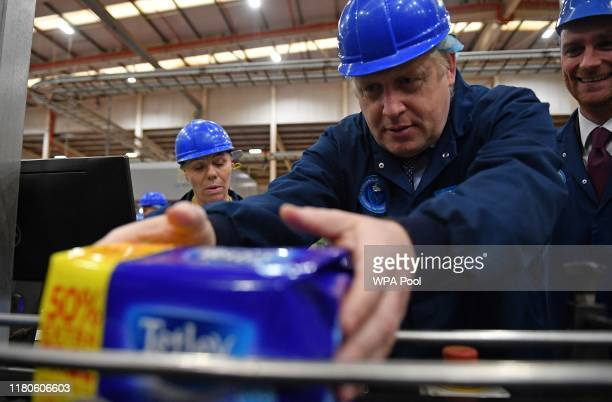 Prime Minister Boris Johnson helps weigh packaged tea bags during a general election campaign visit to the Tetley Tea Factory at Tata Global...
