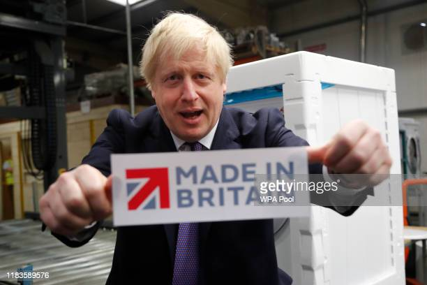 Prime Minister Boris Johnson holds a 'Made In Britain' sign he took off the packaging of a washing machine during a visit to Ebac electrical...