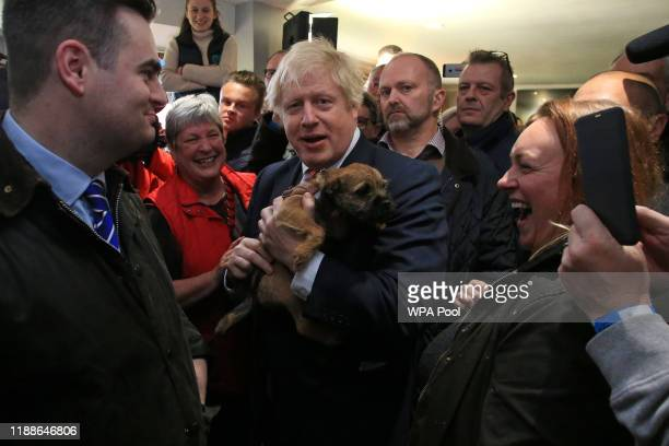 Prime Minister Boris Johnson holds a supporter's dog during a visit to meet newly elected Conservative party MP for Sedgefield, Paul Howell at...