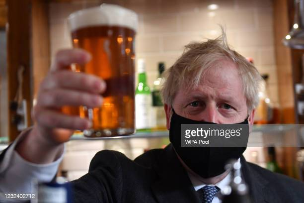 Prime Minister Boris Johnson holds up a pint during a visit to The Mount pub and restaurant on April 19, 2021 in Wolverhampton, United Kingdom. The...