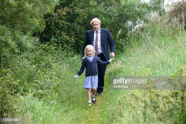 Prime Minister Boris Johnson is escorted by Beatrix Collins, aged 7, who was the runner up in a G7 biodiversity poster competition, as he visits the...