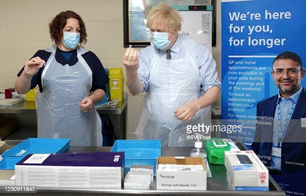 Prime Minister Boris Johnson is shown how to prepare the vaccine by advance nurse practitioner Sarah Sowden as he visits a COVID-19 vaccination...