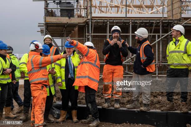 Prime Minister Boris Johnson jokes with builders during a visit to the Barratt Homes Willow Grove housing development on November 21 2019 in Bedford...