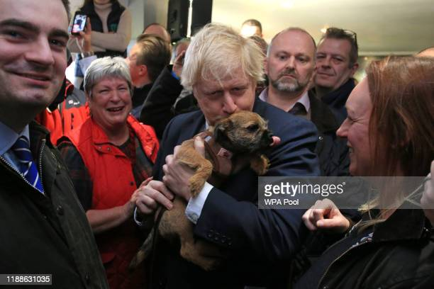 Prime Minister Boris Johnson kisses a supporter's dog during on a visit to meet newly elected Conservative party MP for Sedgefield, Paul Howell at...