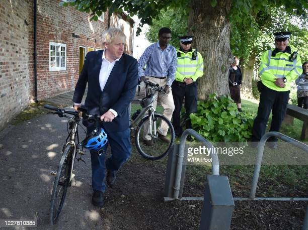 Prime Minister Boris Johnson, left with Darren Henry the Conservative MP for Broxtowe, pushes his cycle at the Canal Side Heritage Centre on July 28,...