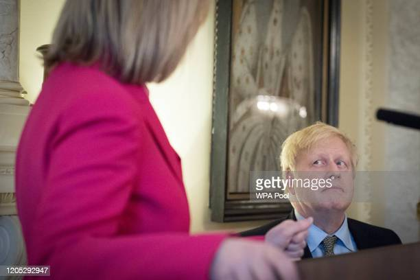 Prime Minister Boris Johnson listens to Liz Truss as they take part in a panel event and reception to mark International Women's Day at Downing...