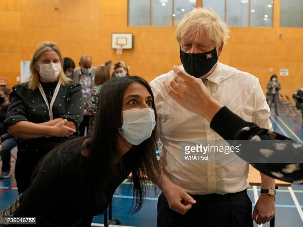 Prime Minister Boris Johnson looks as staff dilute a dose of the pfizer vaccine before administering it as he visits a COVID-19 vaccination centre at...