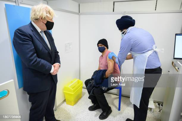 Prime Minister Boris Johnson looks on as a man receives a dose of the AstraZeneca Covid-19 vaccination at a branch of the Boots pharmacy chain,...