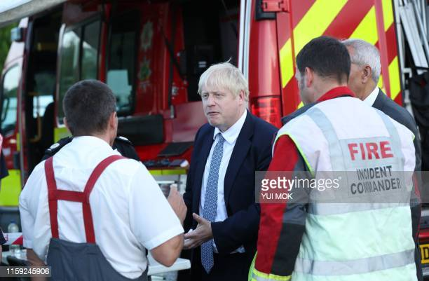 Prime Minister Boris Johnson meets emergency crews at Whaley Bridge Football Club in Derbyshire as work continued at Toddbrook reservoir after severe...