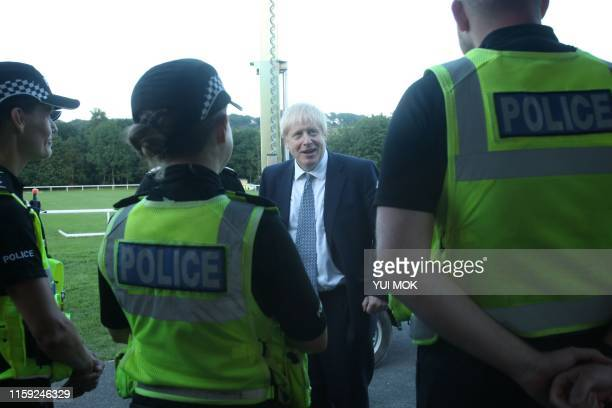 Prime Minister Boris Johnson meets police officers at Whaley Bridge Football Club in Derbyshire as work continued at Toddbrook reservoir after severe...