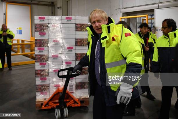 Prime Minister Boris Johnson moves a pallet of chocolate biscuits in a 25 degree celsius storage unit during a general election campaign visit to the...