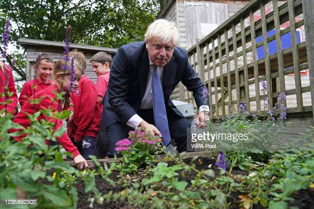 Prime Minister Boris Johnson plants flower bulbs with school children during a visit to Westbury-On-Trym Church of England Academy, prior to a...