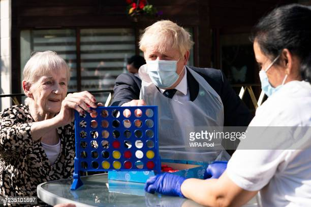 Prime Minister Boris Johnson plays Connect 4 with resident Janet and carer Lakshmi during a visit to Westport Care Home in Stepney Green, ahead of...