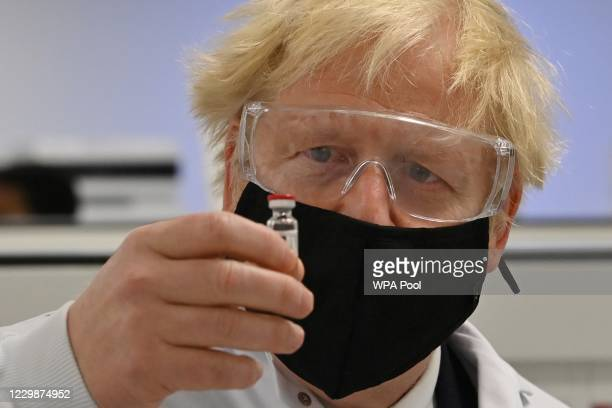 Prime Minister Boris Johnson poses for a photograph with a vial of the AstraZeneca/Oxford University COVID-19 candidate vaccine, known as AZD1222, at...