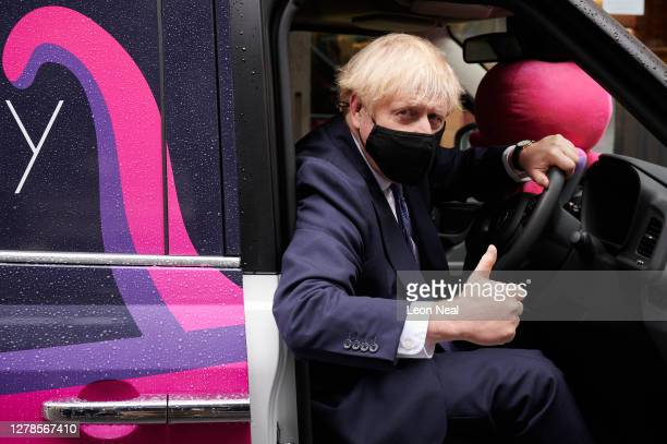Prime Minister Boris Johnson poses for photographs with a branded electric taxi as he visits the headquarters of Octopus Energy on October 05, 2020...