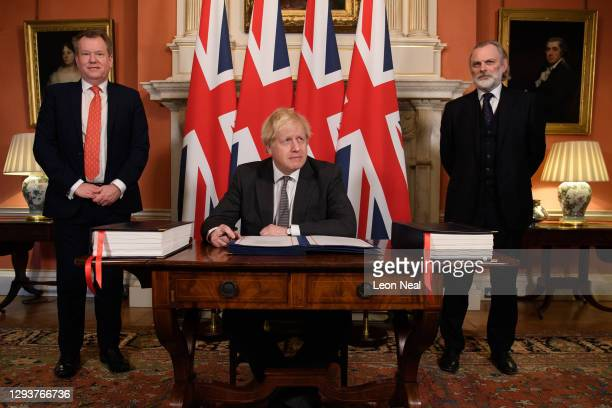 Prime Minister, Boris Johnson poses for photographs with UK chief negotiator David Frost and UK Ambassador to the EU Tim Barrow after signing the...