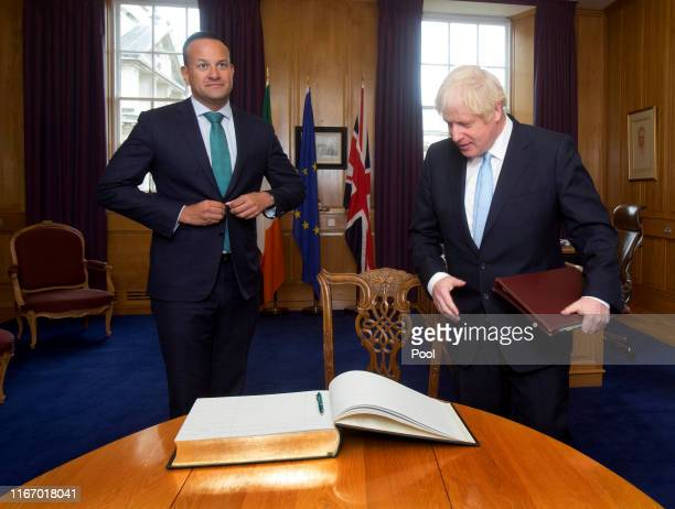 Prime Minister Boris Johnson prepares to sign the visitor's book as Taoiseach Leo Varadkar welcomes him to the Government Buildings during his visit...