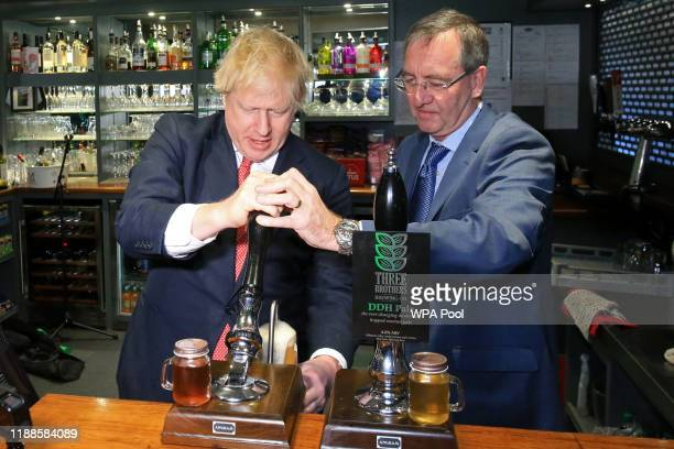 Prime Minister Boris Johnson pulls a pint with newly elected Conservative party MP for Sedgefield, Paul Howell at Sedgefield Cricket Club in County...