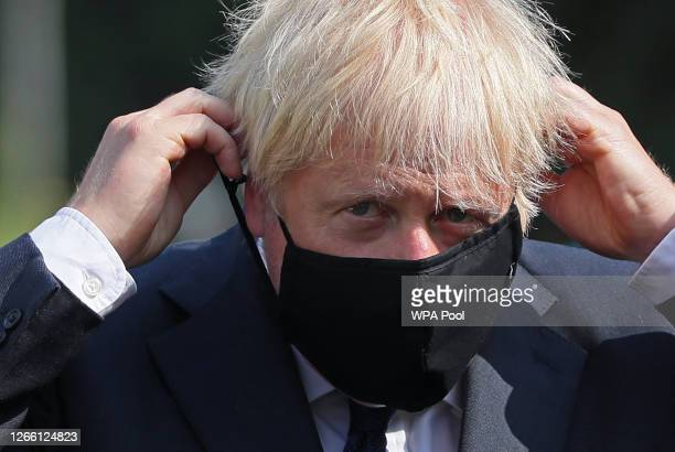 Prime Minister Boris Johnson puts on a face mask at the Northern Ireland Ambulance Service HQ during the Prime Minister's visit to Belfast on August...
