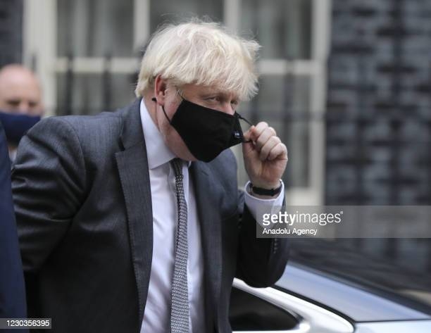 Prime Minister Boris Johnson removes his mask as he returns to number 10 Downing Street after attending Parliament in London, United Kingdom on...