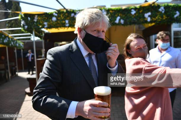 Prime Minister Boris Johnson removes his mask to enjoy a pint in the beer garden during a visit to The Mount pub and restaurant on April 19, 2021 in...