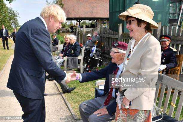 Prime Minister Boris Johnson shakes hands with veteran Arnold Hutchinson from the Parachute Regiment following a national service of remembrance...
