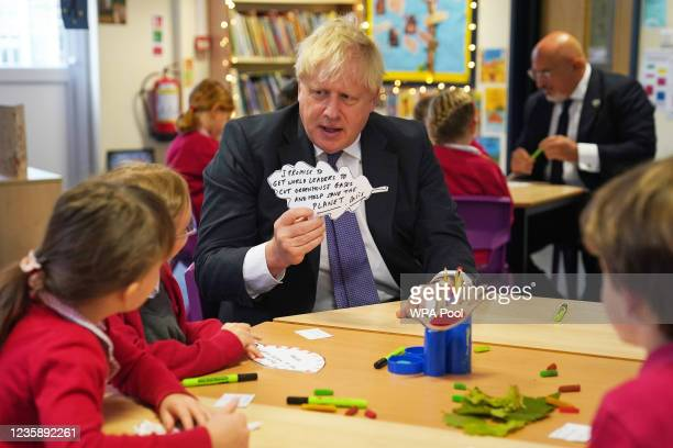 Prime Minister Boris Johnson shows a paper leaf he created to school children during a visit to Westbury-On-Trym Church of England Academy, prior to...