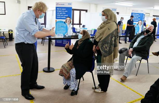 Prime Minister Boris Johnson shows thumbs up to patients after they were given the vaccine as he visits a COVID-19 vaccination centre in Batley, on...