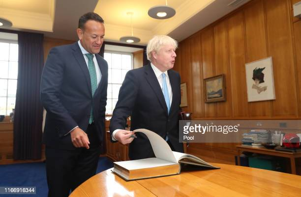 Prime Minister Boris Johnson signing the visitors' book as Taoiseach Leo Varadkar welcomes him to the Government Buildings during his visit on...