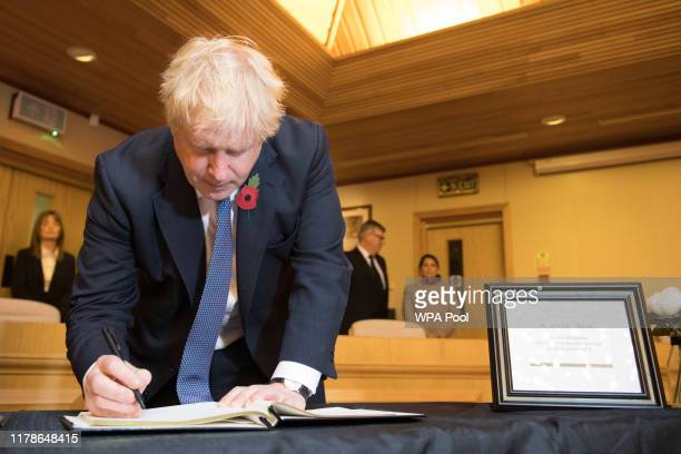 Prime Minister Boris Johnson signs a book of condolence during a visit to Thurrock Council Offices on October 28 2019 in Grays England The bodies of...
