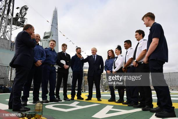 K Prime Minister Boris Johnson speaks to apprentices accompanied by Britain's Defence Secretary Ben Wallace as he visits the NLV Pharos a lighthouse...