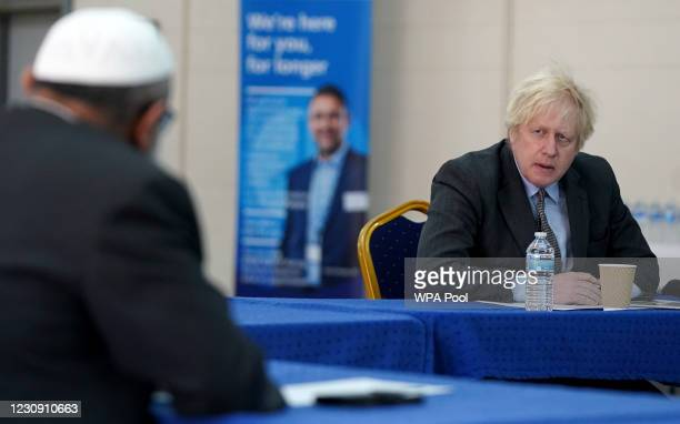 Prime Minister Boris Johnson speaks to members of staff as he visits a COVID-19 vaccination centre in Batley, on February 1, 2021 in West Yorkshire,...