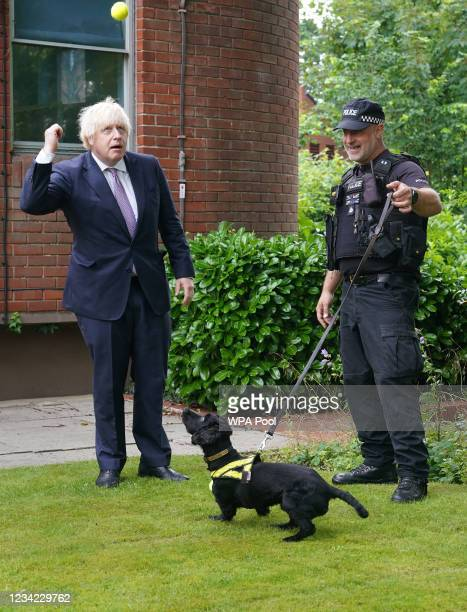 Prime Minister Boris Johnson speaks to Sergeant Dog Handler Mike Barnes as he throws a ball for six year old cocker spaniel Rebel, a proactive drugs...