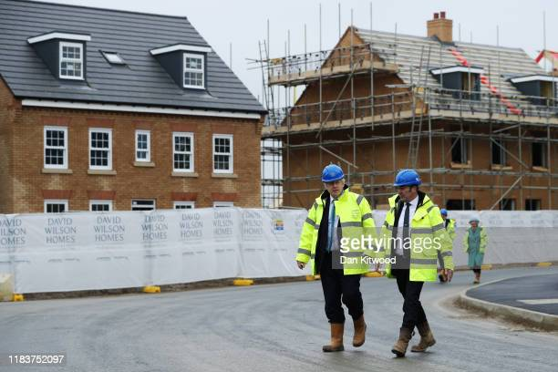 Prime Minister Boris Johnson speaks with Andrew Swindell Regional Director of Barratt Homes during a visit to the Barratt Homes Willow Grove housing...