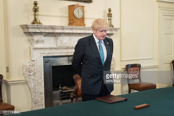 Prime minister Boris Johnson, stands inside the Cabinet Room of 10 Downing Street, London, to observe a minute's silence in tribute to the NHS staff...