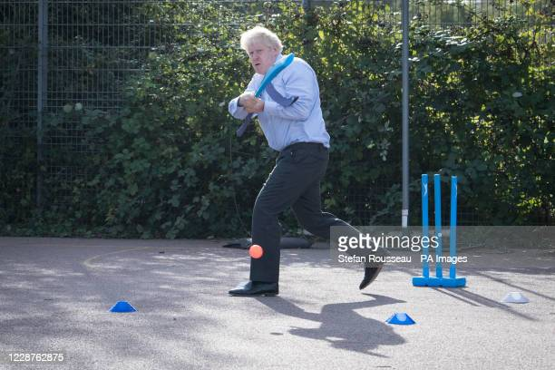 Prime Minister Boris Johnson takes part in a game of cricket during a sports lesson during a visit to Ruislip High School in his constituency of...