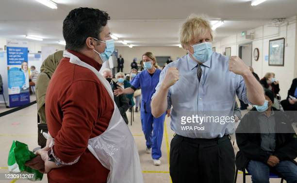 Prime Minister Boris Johnson talks to Christopher Nicholls who suffered from Covid at the same time as Johnson, as he visits a COVID-19 vaccination...
