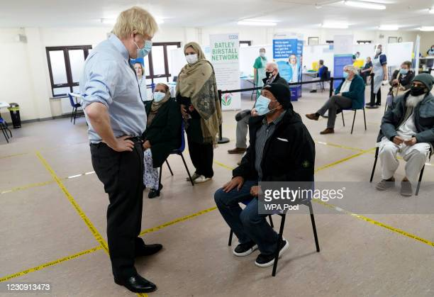 Prime Minister Boris Johnson talks to waiting patients as he visits a COVID-19 vaccination centre in Batley, on February 1, 2021 in West Yorkshire,...