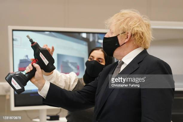 Prime minister Boris Johnson tries out a power tool during a visit to BAe Systems at Warton Aerodrome on March 22, 2021 in Preston, England. The...